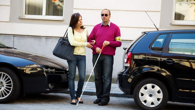 Frau hilft blindem Mann über die Strasse