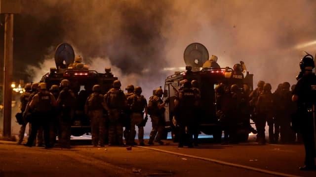 Gepanzerte Fahrzeuge und Polizisten sperren eine Strasse in der Nacht.