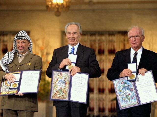 Friedensnobelpreisträger mit ihrer Urkunde.