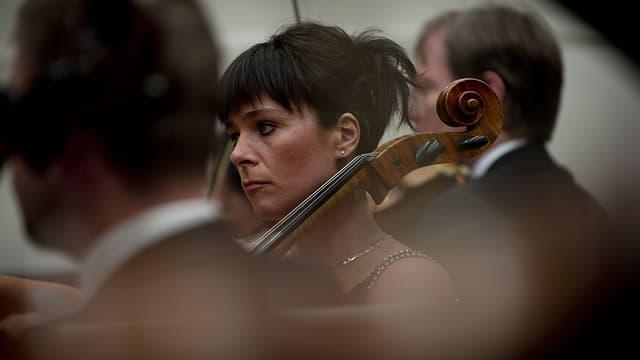 Nahaufnahme von zwei Musikern und einer Musikerin mit Cello im Zürcher Kammerorchester.