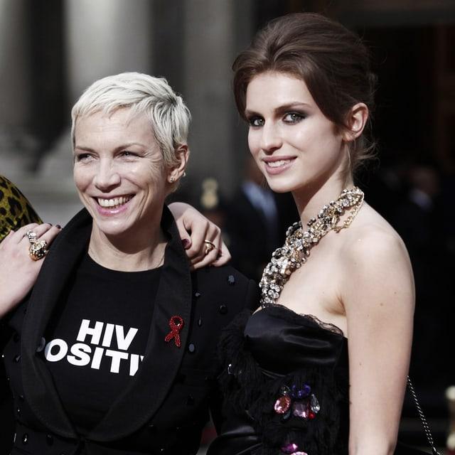 Links eine Frau mit kurzen blonden Haaren, rechts die Tochter mit braunen Haaren vor schwarzem Hintergrund