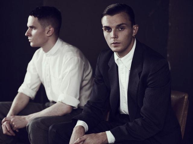 Zwei Männer in Anzügen mit gegelten Haaren