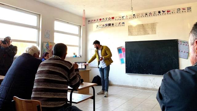 Bauern von Anë Vjosë in einer Schule. Vorne steht ein Redner der Investoren.