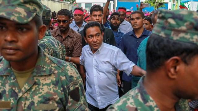 Yameen im Hemd umringt von Soldaten-Leibwächtern.