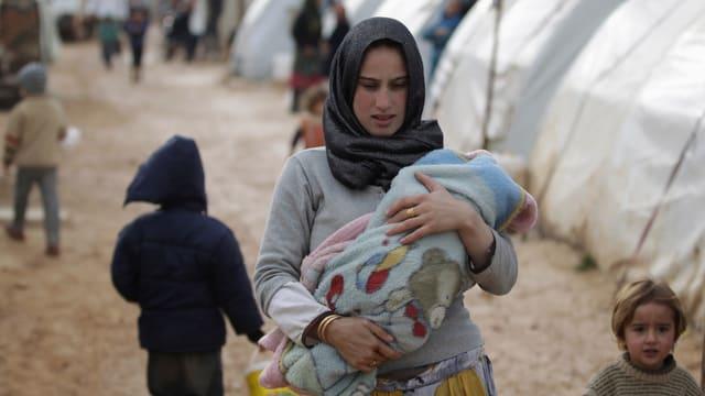 Eine junge Frau mit Kopftuch in einem Durchgangsweg einer Zeltstadt, im Arm hält sie einen Säugling, daneben ein kleines Mädchen.