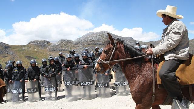 Ein Mann mit Hut reitet an an einer Reihe Polizisten hinter Schutzschildern vorbei.
