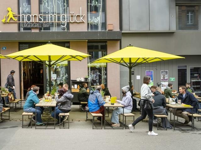 Personen auf Sitzplätzen vor einem Restaurant in Basel.