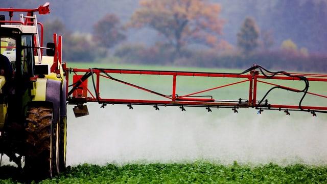 Ein Traktor versprüht Pestizide auf einem Acker.