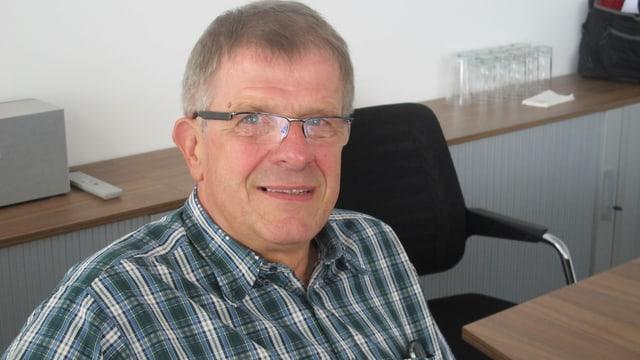Werner Schmid sitzt auf einem Stuhl.