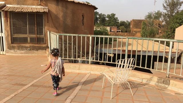 Ein kleines Kind von hinten auf einer Terassee.