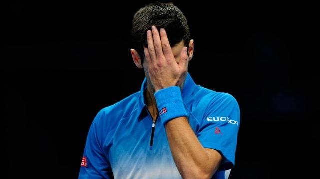 Novak Djokovic hält sich nach seiner Niederlage gegen Roger Federer seine linke Hand vors Gesicht.