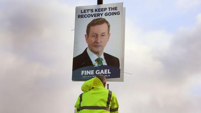 Ein Arbeiter befestigt ein Wahlplakat von Premier Kenny an einem Mast.
