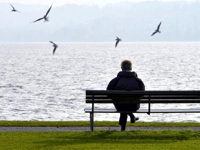 Mann auf Bank am See.