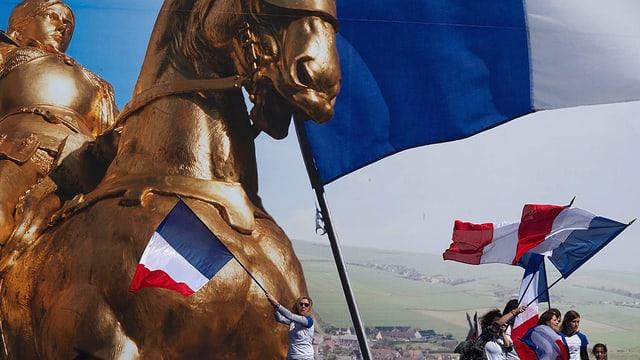 Ein goldenes Pferd und Frankreich-Flaggen werden während einer Veranstaltung von Anhängern des Front National hochgehalten.