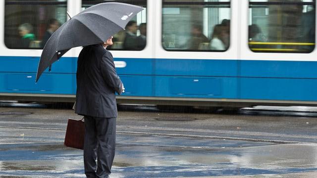 Mann in Anzug und mit Aktentasche und offenem Regenschirm vor einem Zürcher Tram.