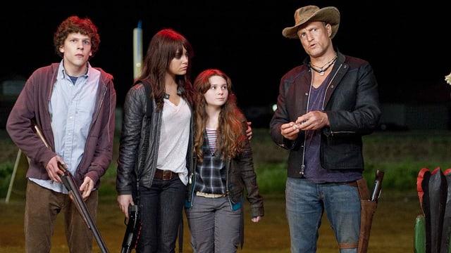4 Leute, einer mit Gewehr stehen nebeneinander und wirken verängstigt.
