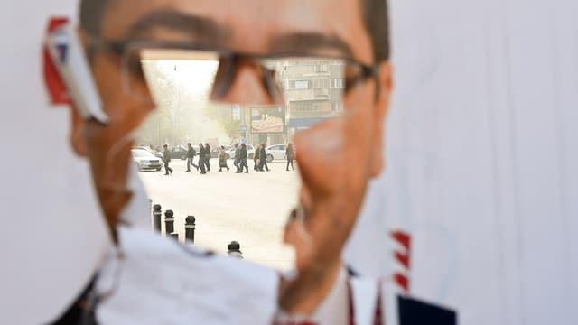 Durch ein zerrissenes Wahlplakat sind Menschen auf einer Strasse zu sehen.