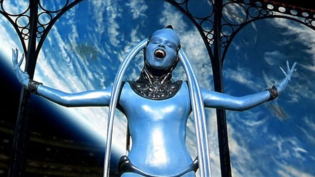 Eine Frau in blauem Kostüm singt und hält die Arme in die Luft.