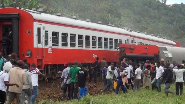 Menschen scharen sich in Kamerun nach Zugunglück um die entgleisten Waggons.