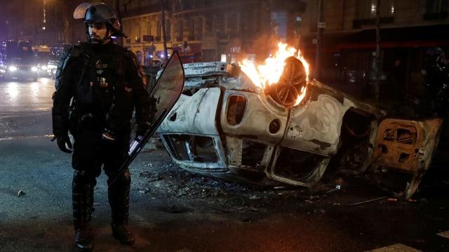 Polizist neben brennendem Auto