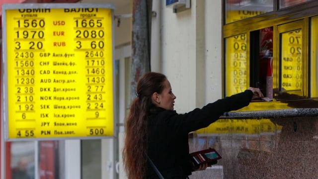 Eine Frau wechselt Geld in der Ukraine.