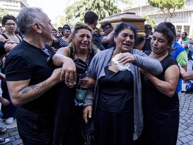 Menschen nehmen an einem Beerdigungsumzug teil, sie trauern.