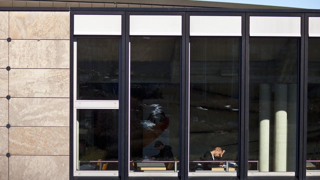 Student hinter einer Fensterfront