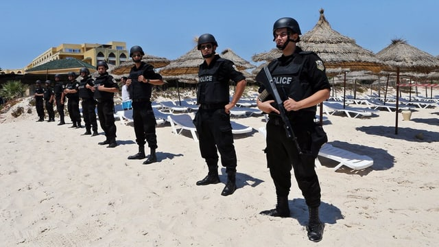 Policits che stattan guardia tar ina riva a Sousse.