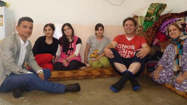 Andreas Goerlich sitzt mit einer syrischen Flüchtlingsfamilie am Boden.