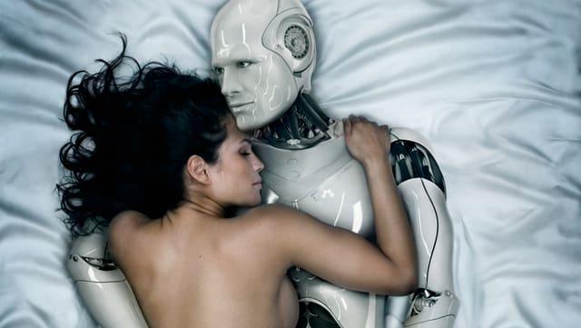 Roboter und Frau umarmen sich im Bett.