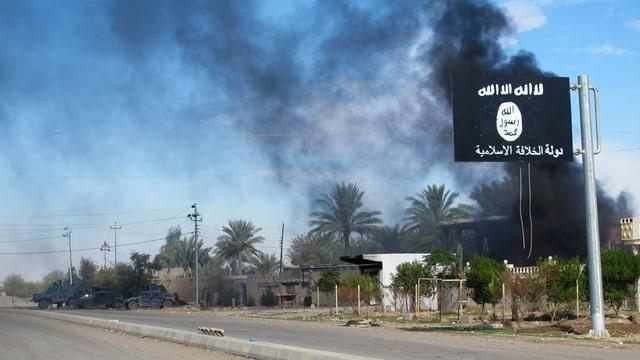 Zu sehen ist eine schwarze IS-Flagge mit weissen arabischen Schriftzeichen. Dahinter eine Stadt mit Palmen, aus welcher schwarzer Rauch aufsteigt