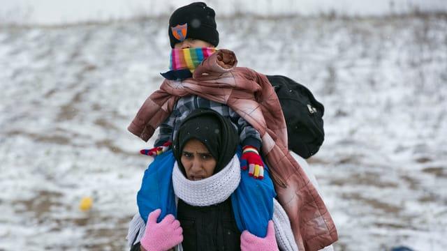 Eine Mutter trägt ein dick eingpacktes Kind mit schwerem Rucksack auf den Schultern über ein Schneefeld.