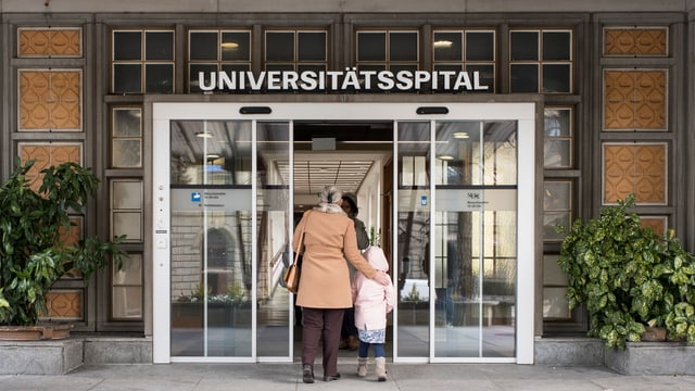 Eine ältere Frau läuft mit einem kleinen Mädchen ins Zürcher Universitätsspital.