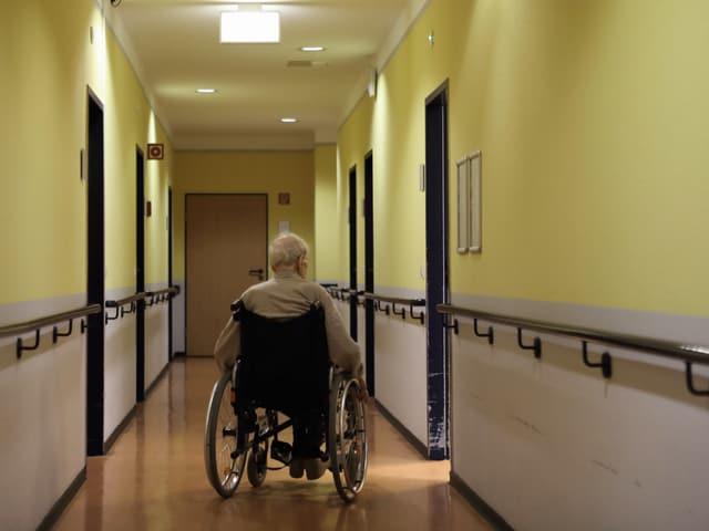 Ein alter Mann im Rollstuhl in einem Gang