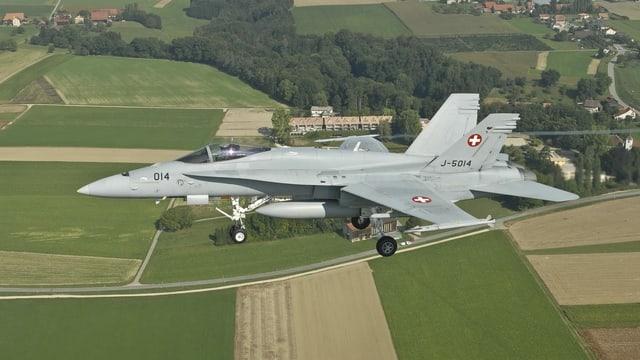 Kampfjet fliegt über Felder.
