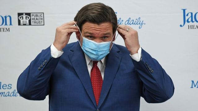 Ron DeSantis legt sich eine Hygienemaske an.