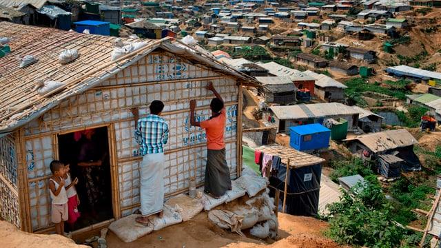 Flüchtlinge bauen eine Hütte zusammen