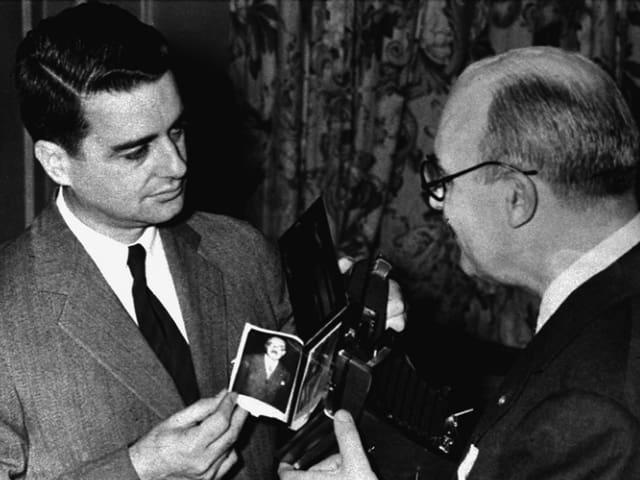 Mann mit Foto in der Hand.