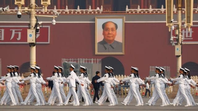 Matrosen defilieren vor einem Bild von Mao Zedong vorbei.