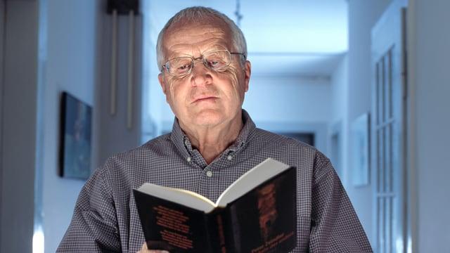 Peter Zeindler liest stehend eines seiner Bücher.