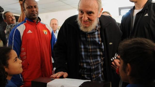 Fidel Castro gibt seine Stimme ab. Im Vordergrund zwei kleine Kinder. Links von Castro ein Mann im Trainingsanzug.