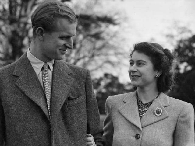 Ein junges Paar lächelt sich verliebt an. Beide im Anzug. Das Bild ist schwarz-weiss.