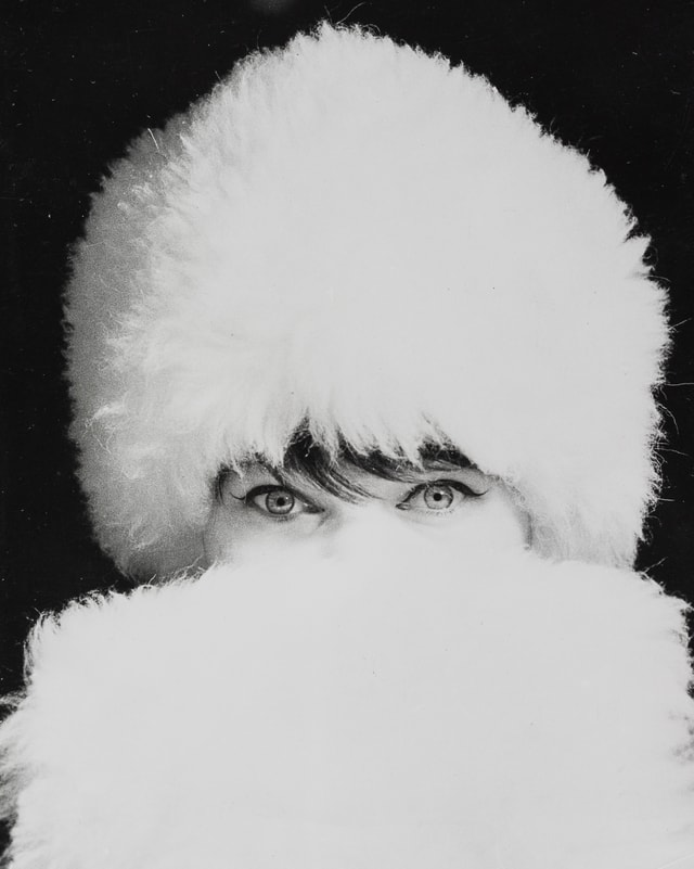 Schwarz-Weiss-Foto: Eine Frau mit weissem Pelzhut verdeckt ihr Gesicht so mit einem weissen Pelz, dass nur noch ihre Augen zu sehen sind.