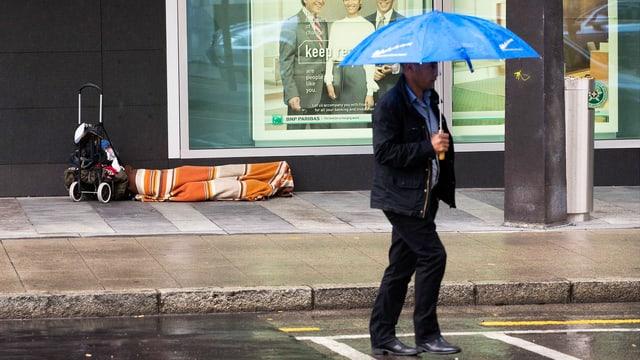 Ein Mann geht über die Strasse. Im Hintergrund ist eine Person zu sehen, die in eine Decke gehüllt am Strassenrand liegt.