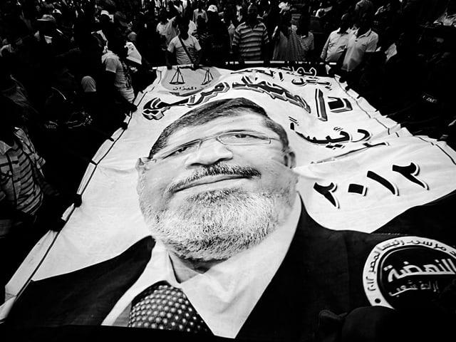 Schwarz-Weiss-Foto: Menschen halten eine grosse Fahne mit dem Bild von Mohammed Mursi. Durch die Unebenheiten der Fahne ist das Gesicht verzerrt.