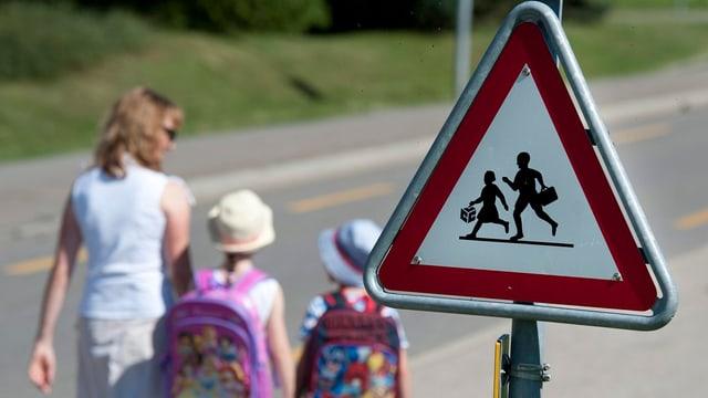 Eine Mutter begleitet Ihre Kinder auf dem Schulweg.