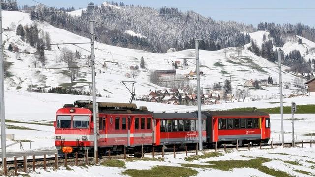Ein roter Zug mit drei Waggons rollt durch eine Winterlandschaft.