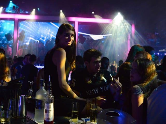 Eine junge Frau steht in einem Nachtclub an einer Bar.