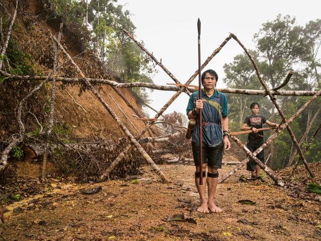Ein Mitglied der Penan vor einer Sperre.
