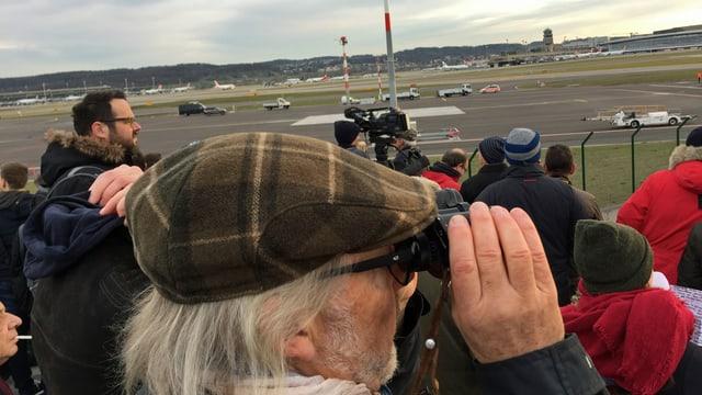 Mann mit grauen Haaren und Kappe sieht mit Feldstecher auf den Flughafen